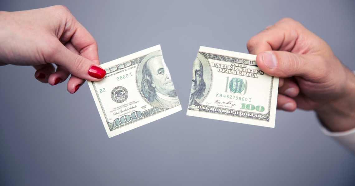 Concept image of a female and male hand dividing money