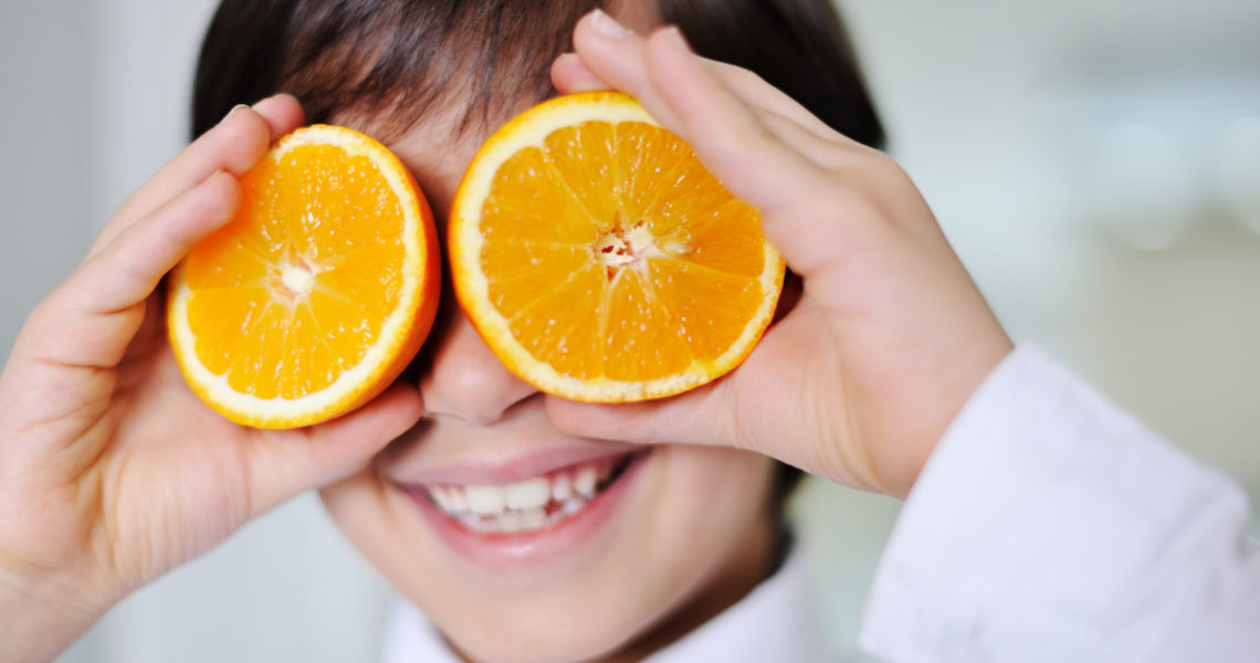 Little kid hplaying with fresh orange fruits